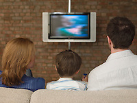 Boy Between Parents Watching Television