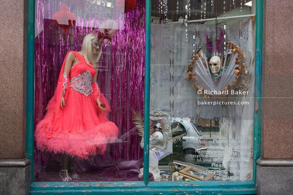 Garish costume on sale in a charity shop window, East Dulwich South London.