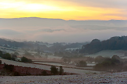 © Licensed to London News Pictures. 19/11/2019. Brecon, Powys, Wales, UK. The sun rises over the Mynydd epynt range looking towards the  Brecon Beacons National Park. Temperatures dropped to several degrees C below zero last night and remained low during the morning near Builth Wells in Powys, UK. Photo credit: Graham M. Lawrence/LNP
