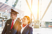 Portrait of mature pilot and attractive flight attendant walking while smiling in airport