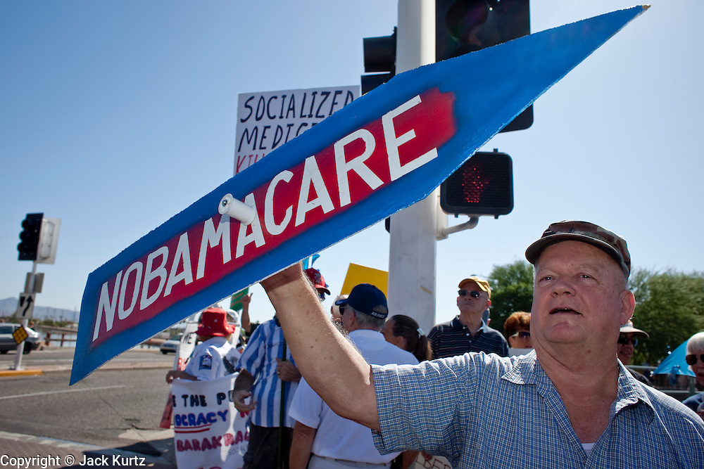 Aug. 8, 2009 -- SCOTTSDALE, AZ: LANCE STEWART, from Mesa, AZ, spins a sign expressing his opposition to the Obama health care plan at a rally in Scottsdale, AZ, Saturday. Nearly 1,000 people opposed to the President Barack Obama's health care reform efforts picketed the offices of Congresman Harry Mitchell (D-AZ) in Scottsdale, AZ, Saturday. The protest was organized by conservative groups who are organizing similar protests against President Obama across the US. Ostensibly concerned mostly with health care reform, it was also a protest against almost everything related to the Obama administration. Photo by Jack Kurtz / ZUMA Press