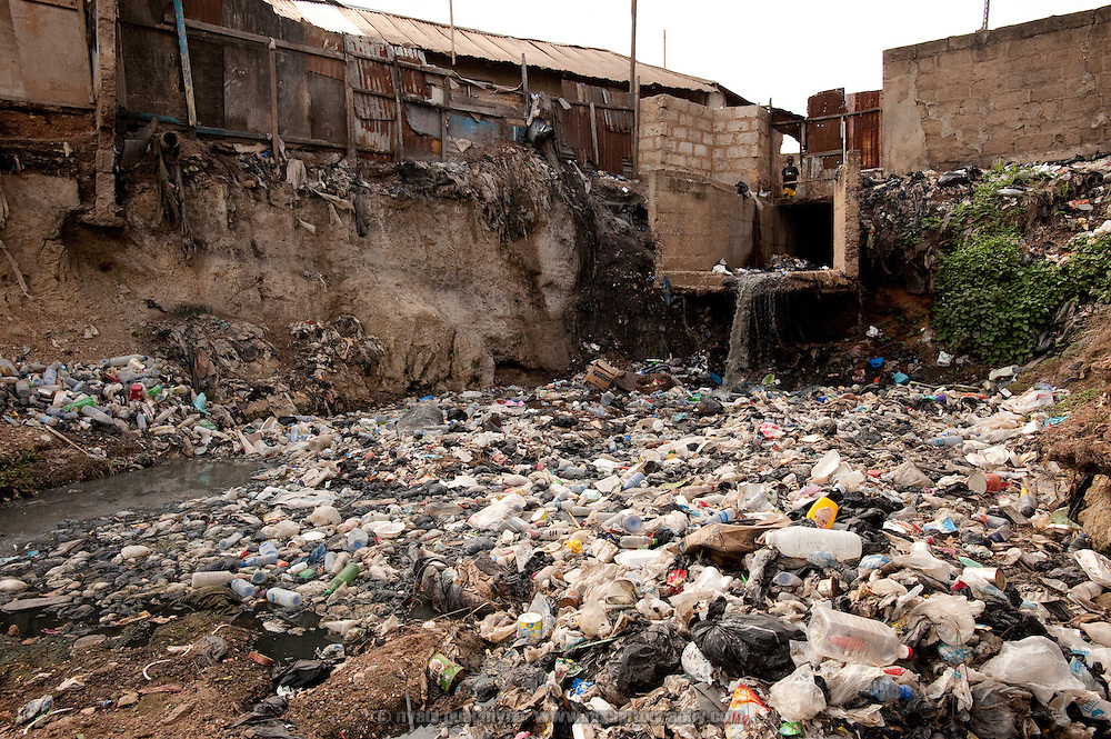 A severely polluted river divides east and west Nima, a densely populated area of Ghana's capital, Accra. Both sides of the community slope down to the river,  washing trash and debris into the watercourse when it rains. In addition, in the absence of adequate waste collection and sanitation, the river serves as a de facto dumping ground and a latrine. Sanitation workers regularly clear the waterway, but refuse is not collected, only raked to the banks to allow the water to flow. The refuse seen here is floating atop a pool which is avoided by sanitation workers because of its depth.