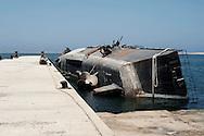 Libya, Tripoli: A sunken by 2011 NATO airstrikes warship lies on a side in the NAVI port of Tripoli.  Alessio Romenzi