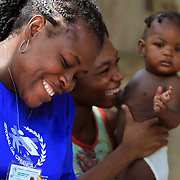 A volunteer and mother and child laugh together during a home visit in Grand Bassin, Haiti.