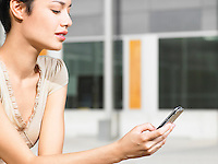 Young woman sitting in plaza sending text message close up