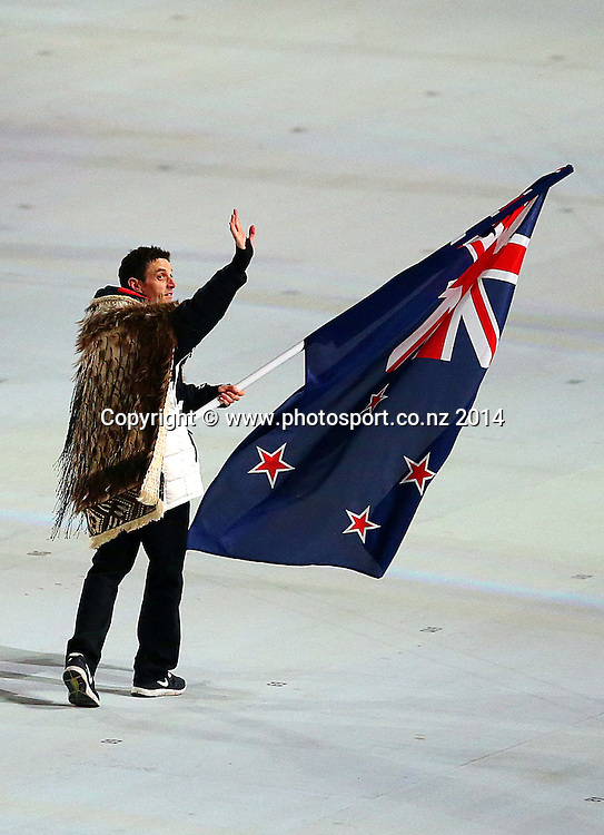 New Zealand's flag bearer Shane Dobbin  enters the stadium during the Sochi 2014 Winter Olympics Opening Ceremony in the Fisht Olympic Stadium on February 7, 2014 in Sochi, Russia. Photo: Ian MacNicol/www.photosport.co.nz