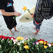 Participants are given floers before the paddle-out in memory of Molly Rowlee, at Wrightsville Beach, NC. The event also helped support the Molly Fund, a non-profit dedicated to helping children with lymphoma and their families.