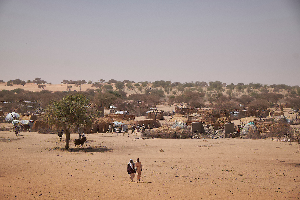 Men walk towards sand dunes in the village of Guidan Kaji near the border with Nigeria on the outskirts of Diffa, Niger on February 13, 2016. Displaced people from Niger and Nigeria are sheltering in the village after fleeing at the nearby border. Many of the families had witnessed attacks by Boko Haram in their villages or had fled because of other villages around them being attacked. Caritas undertook a distribution of sleeping covers, mosquito nets, pots and money transfers.
