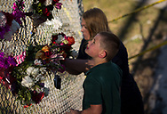 "Brayden Meddaugh, 7, and his mother, Stefanie Mion, both of Deerfield Beach, pay their respects at a small makeshift memorial under the Sawgrass Expressway, across from the entrance to Marjory Stoneman Douglas High School in Parkland on Thursday, Feb. 15, 2018, following Wednesday's school shooting. ""I grew up in the area, and knew a lot of the people that responded,"" Mion said. (XAVIER MASCAREÑAS/TREASURE COAST NEWSPAPERS)"