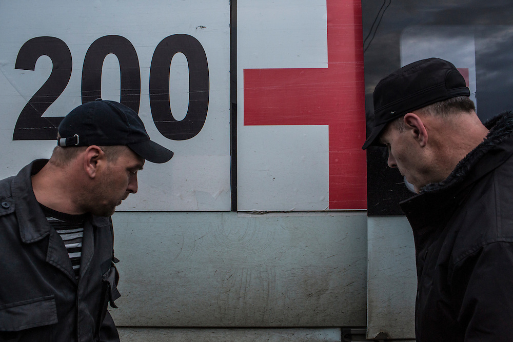 Yevgeny Kishkin, age 31, from Kakhovka in the Kherson region (left) and Igor Slyusar, age 40, from Kiev, both members of the Black Tulips, stand outside the vehicle they use to collect unclaimed bodies on Wednesday, April 9, 2015 in Velyka Novosilka, Ukraine.