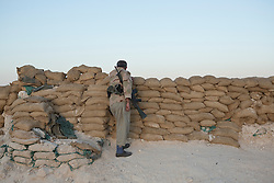 © Licensed to London News Pictures. 02/09/2015. Bashiqa, Iraq. As day breaks a Kurdish peshmerga fighter mans a sandbagged defensive position on Bashiqa Mountain, Iraq.<br /> <br /> Bashiqa Mountain, towering over the town of the same name, is now a heavily fortified front line. Kurdish peshmerga, having withdrawn to the mountain after the August 2014 ISIS offensive, now watch over Islamic State held territory from their sandbagged high-ground positions. Regular exchanges of fire take place between the Kurds and the Islamic militants with the occupied Iraqi city of Mosul forming the backdrop.<br /> <br /> The town of Bashiqa, a formerly mixed town that had a population of Yazidi, Kurd, Arab and Shabak, now lies empty apart from insurgents. Along with several other urban sprawls the town forms one of the gateways to Iraq's second largest city that will need to be dealt with should the Kurds be called to advance on Mosul. Photo credit: Matt Cetti-Roberts/LNP