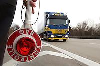03 JAN 2005, LUDWIGSFELDE/GERMANY:<br /> Beamter des Bundesamtes fuer Gueterverkehr mit Kelle, waehrend einer Mautkontrolle, Parkplatz Fresdorfer Heide<br /> IMAGE: 20050103-01-007<br /> KEYWORDS: Bundesamt f&uuml;r G&uuml;terverkehr, LKW Maut, Kontroleur<br /> BAG