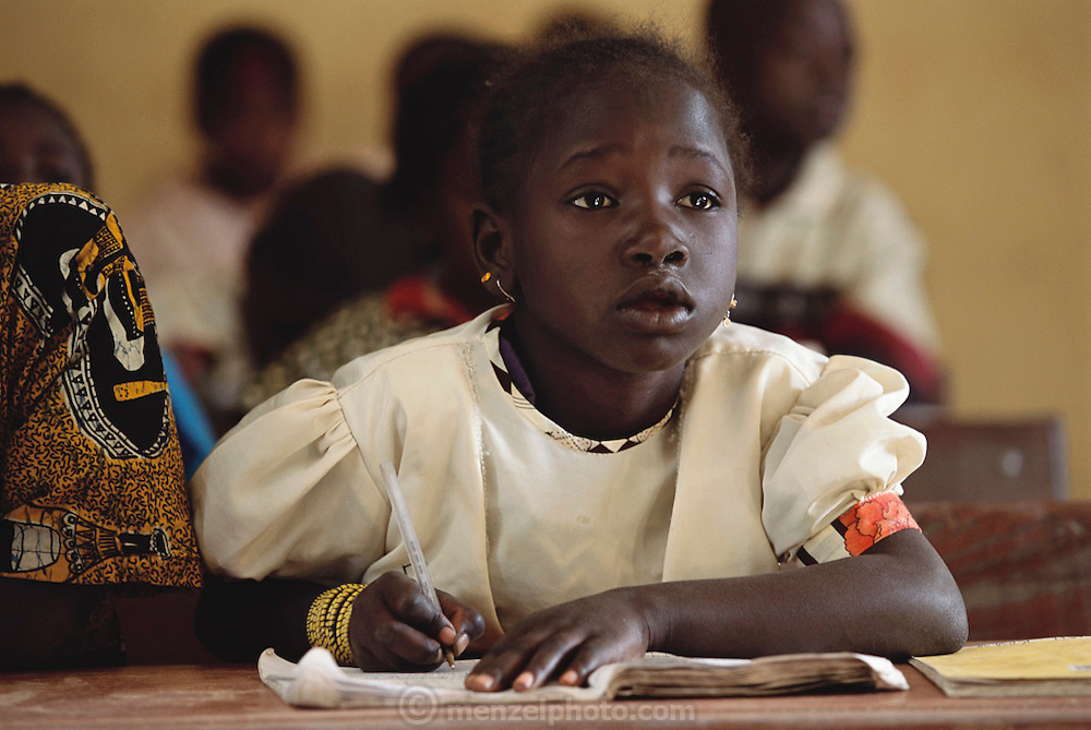 A young girl pays attention to her teacher in math class in Kouakourou village public school, Mali. Africa, Child, Children, Education. From coverage of revisit to Material World Project family in Mali, 2001.