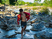 18 JUNE 2016 - DON KHONE, CHAMPASAK, LAOS: A fisherman walks back to shore at Khon Pa Soi Waterfalls, on the east side of Don Khon. It's the smaller of the two waterfalls in Don Khon. Fishermen have constructed an elaborate system of rope bridges over the falls they use to get to the fish traps they set. Fishermen in the area are contending with lower yields and smaller fish, threatening their way of life. The Mekong River is one of the most biodiverse and productive rivers on Earth. It is a global hotspot for freshwater fishes: over 1,000 species have been recorded there, second only to the Amazon. The Mekong River is also the most productive inland fishery in the world. The total harvest of fish from the Mekong is approximately 2.5 million metric tons per year. By some estimates the harvest in the Tonle Sap (in Cambodia) had doubled from 1940 to 1995, but the number of people fishing the in the lake has quadrupled, so the harvest per person is cut in half. There is evidence of over fishing in the Mekong - populations of large fish have shrunk and fishermen are bringing in smaller and smaller fish.     PHOTO BY JACK KURTZ