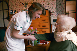 Carer helping an elderly woman to dress; homecare for the elderly,
