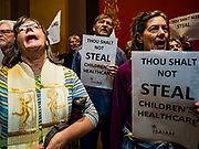 "04 MAY 2017 - ST. PAUL, MN: People from Isaiah - Faith in Democracy pray in the hallway in front of the Minnesota State Senate during a demonstration in front of the Senate. About 200 people participated in a ""ISAIAH's 100 Days of Prophetic Resistance"" rally at the Minnesota State Capitol in St. Paul. They represented churches from across the Twin Cities and were demonstrating in favor of paid sick leave, child care, and a higher minimum wage. The Twin Cities are more liberal than rural Minnesota and many Twin Cities municipalities have passed ordinances with paid sick leave, child care and higher minimum wages. Republican legislators from rural Minnesota have tried to pass laws in the legislature rolling back those ordinances.     PHOTO BY JACK KURTZ"