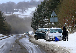 © Licensed to London News Pictures. 12/03/2013, Hayward Heath, UK.  A man prepares to recover his abandoned car by a snow covered road side near Hayward Heath, West Sussex, England, as roads are affected by snow fall, Tuesday, March 12, 2013. Photo credit : Sang Tan/LNP