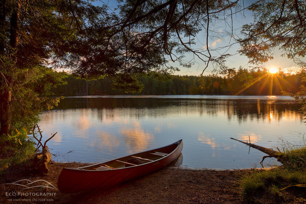 Canoe at sunrise on the shore next to Zack Woods Pond in Hyde Park, Vermont. HDR. Green River Reservoir State Park