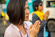 24 NOVEMBER 2012 - BANGKOK, THAILAND:  People pray during the opening ceremonies of a large anti government, pro-monarchy, protest  on November 24, 2012 in Bangkok, Thailand. The Siam Pitak group, which sponsored the protest, cited alleged government corruption and anti-monarchist elements within the ruling party as grounds for the protest. Police used tear gas and baton charges againt protesters.       PHOTO BY JACK KURTZ