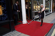 An eccentric woman lifts a leg while hoovering a red carpet in London's Bond Street before Vogue's Fashion's Night Out festival in the streets of the West End. Running the cleaning device across her business' carpet that has been placed across the otherwise drab pavement, the female member of staff makes an impromptu jig while holding the nozzle of the hoover as other employees laugh and giggle at her sudden show of eccentricity.