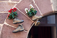 old pilgrim hiking boots haning over the doorway with flowers in them. you will find old boots decorating window ledges, doorways and way markers all along the camino route