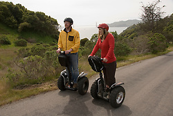 Couple on Segways, each on a Segway, on Angel Island State Park in San Francisco Bay, California, CA. Model released..Photo camari219-70428..Photo copyright Lee Foster, www.fostertravel.com, 510-549-2202, lee@fostertravel.com.