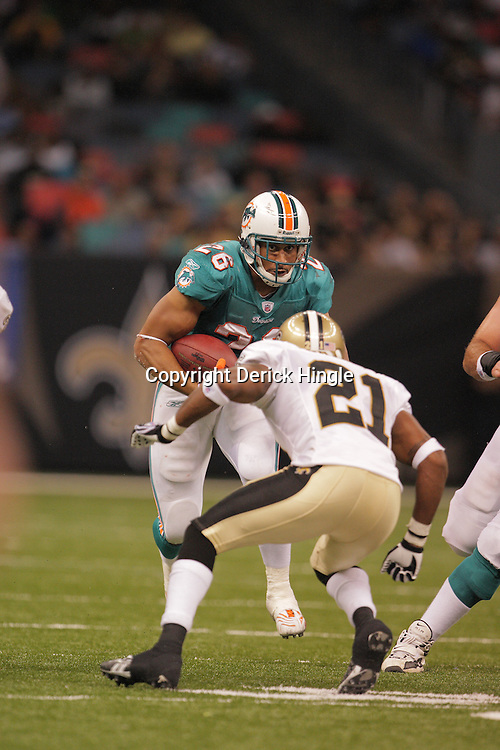2008 August 28: Rookie running back Lex Hilliard (26) of the Miami Dolphins runs towards New Orleans Saints defender Jason Craft (21) during a preseason contest at the Louisiana Superdome in New Orleans, LA.