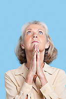 Senior woman praying with hands clasped against blue background