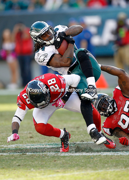 Philadelphia Eagles running back Eldra Buckley (34) gets gang tackled by Atlanta Falcons safety Thomas DeCoud (28) and a Falcons teammate during the NFL week 6 football game against the Atlanta Falcons on Sunday, October 17, 2010 in Philadelphia, Pennsylvania. The Eagles won the game 31-17. (©Paul Anthony Spinelli)