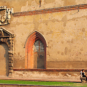 Woman resting on stone bench in courtyard at Sforza Castle, Milan, Italy