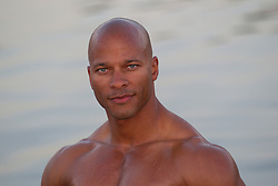 shirtless All American green eyed African American bodybuilder with a shaved head looking at camera