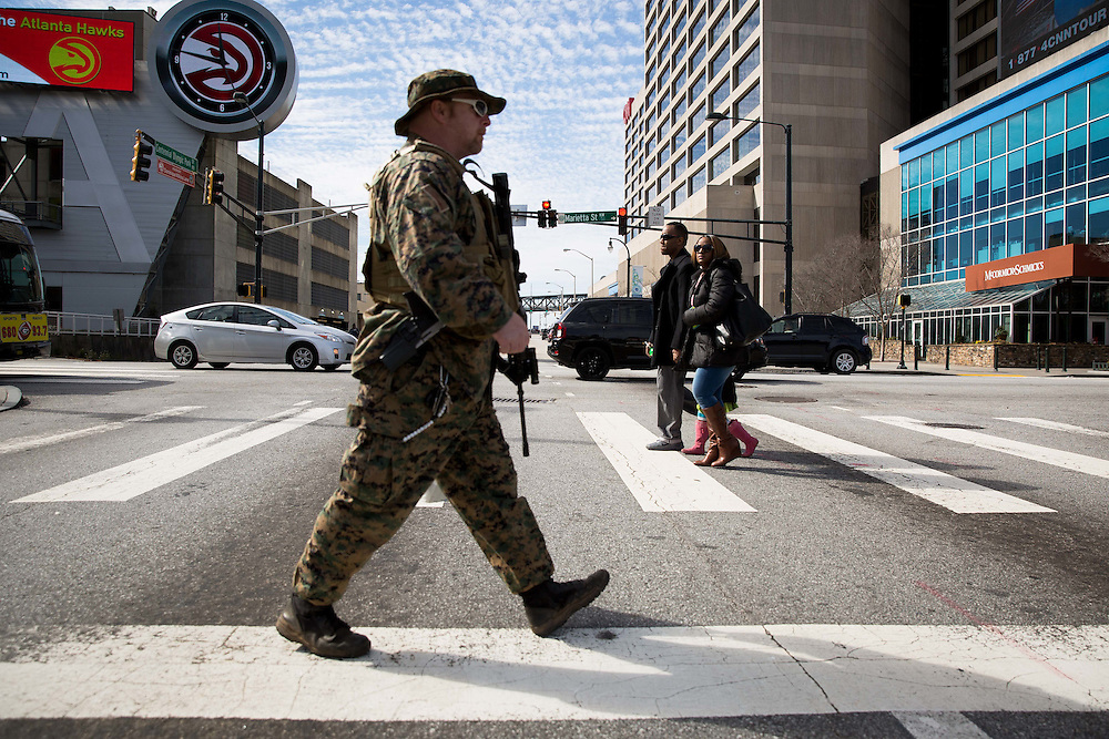The Georgia Security Force III% militia holds a protest on Marietta Street in downtown Atlanta on Saturday, Feb. 6, 2016. The protest was partly inspired by the death of LaVoy Finicum by federal authorities. Here, Chris Hill crosses the street to head to the protest. About a half-dozen people showed up. Photo by Kevin D. Liles/kevindliles.com
