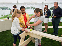 """Girls At Work"" Violet Brier, Sadie Fortune and Kaylee Richard work together to build a picnic table during the Winnipesaukee Wine Festival Thursday evening.  Proceeds raised from the evening will go to the ""Girls At Work"" organization.   (Karen Bobotas/for the Laconia Daily Sun)"