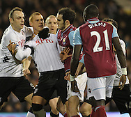 Picture by David Horn/Focus Images Ltd +44 7545 970036.30/01/2013.Steven Sidwell (centre) of Fulham is held back from Mohamed Diame of West Ham by team mate Dimitar Berbatov (left) of Fulham after a high challenge leading to a yellow card during the Barclays Premier League match at Craven Cottage, London.