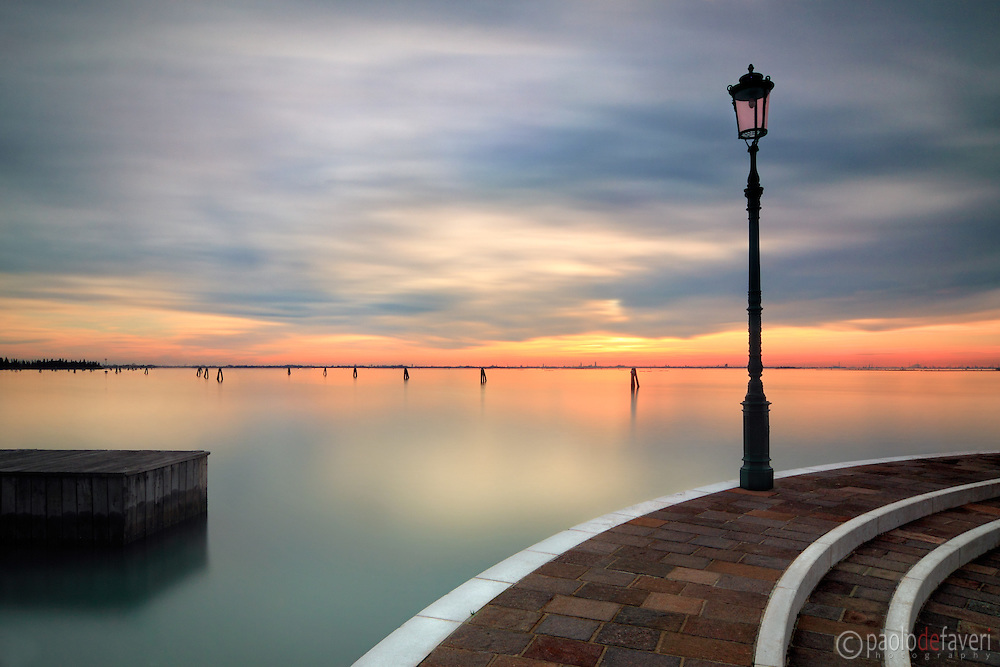 """A view of the Venetian lagoon from the small harbour of Burano, with the downtown Venice skyline in the background. Taken about half hour before sunset, this is an exposure of 120""""."""