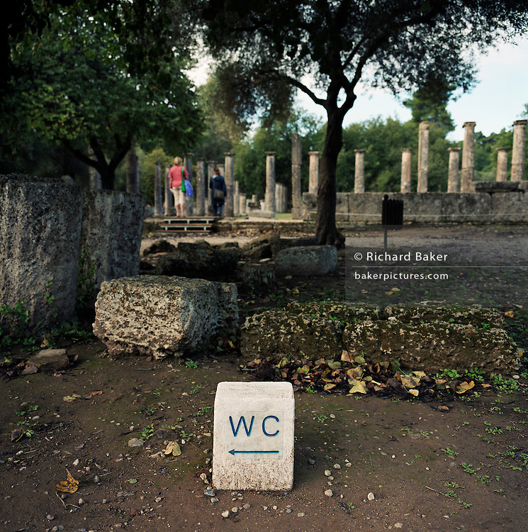 A toilet sign sits near the standing Doric columns and tourists at Olympia's Palaestra or wrestling school. Here, training, instruction and bathing took place in the month before the Games. The 29th modern Olympic circus came home to Greece in 2004 and the birthplace of athletics, amid the woodland of ancient Olympia where for 1,100 continuous years, the ancients held their pagan festival of sport and debauchery. The modern games share many characteristics with its ancient counterpart. Corruption, politics and cheating interfered then as it does now and the 2004 Athens Olympiad echoed both what was great and horrid about the past.