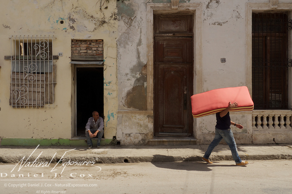A man carries a bed mattress on the streets of Ceinfuegos, Cuba