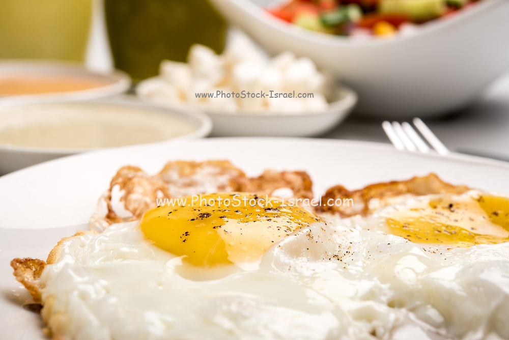 Traditional Israeli Breakfast with two fried eggs, yellow cheese, salad, a fresh roll and a cup of cappuccino. Closeup on the fried eggs
