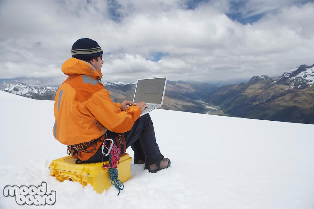 Hiker using laptop on snowy mountain peak back view