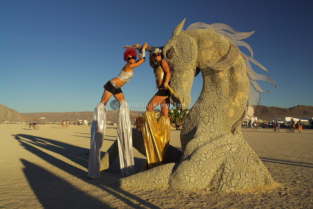 "BLACK ROCK CITY, NV:  Two Burning Man participants on stilts pose in front of a piece of artwork titled ""Playa Anima Rising"" by Mardi Storm in Black Rock City, Nevada."