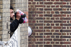 © Licensed to London News Pictures . 11/06/2013 . London , UK . One of those inside the building pokes his head out of the window . Police surround a former police station on 40 Beak Street , Soho this morning (11th June) . The site has been occupied by organisers of today's Stop G8 anti capitalist protests . Demonstrations in London today (Tuesday 11th June 2013) ahead of Britain hosting the 39th G8 summit on 17th/18th June at the Lough Erne Resort , County Fermanagh , Northern Ireland , next week . Photo credit : Joel Goodman/LNP