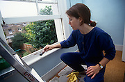 A woman in her late 20s crouches down to paint the bare wood of a window frame in a Victorian terraced home. Wearing blue work overalls and brandishing a narrow width paint brush with white wood primer on its hairs, the lady works away in a rear room of this house that overlooks similar aged properties in south London, England. The sash-style window is up and open so that fresh air helps dry this coat of paint. Furniture has been cleared from the room - a back of the house upstairs bathroom.