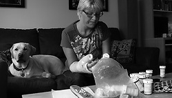 Karen Boyce prepares her medication for the afternoon. MA, 2010.