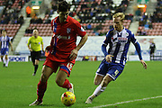 Aaron Morris and Wigan Midfielder David Perkins during the Sky Bet League 1 match between Wigan Athletic and Gillingham at the DW Stadium, Wigan, England on 7 January 2016. Photo by Pete Burns.