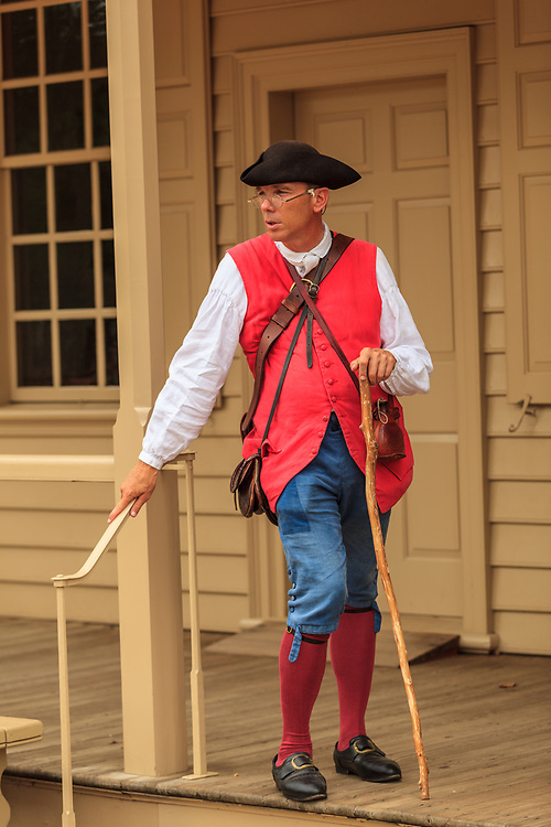 Costumed interpreter holds a walking stick portraying a colonist at Colonial Williamsburg, VA.