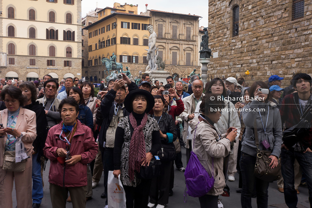 An Asian tour group admires renaissance statues in Florence's Piazza della Signoria. With the tall marble replica statue of Neptune in the background as well as the mounted figure of Cosimo Medici on his horse to the left, the tourists are listening to the amplified commentary of their leader who tells them about the history of this city and its context within the medieval world of art and trade.  The city lies on the River Arno and is known for its history and its importance in the Middle Ages and in the Renaissance, especially for its art and architecture. A centre of medieval European trade and finance and one of the wealthiest cities of the time, Florence has been called the Athens of the Middle Ages.