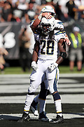 Los Angeles Chargers center Spencer Pulley (73) gives a pat on the helmet to Los Angeles Chargers running back Melvin Gordon (28) after Gordon dives for a second quarter touchdown that ties the score at 7-7 during the 2017 NFL week 6 regular season football game against the against the Oakland Raiders, Sunday, Oct. 15, 2017 in Oakland, Calif. The Chargers won the game 17-16. (©Paul Anthony Spinelli)