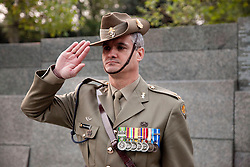 © licensed to London News Pictures. ANZAC MEMORIAL, LONDON, UK  25/04/11. An Australian soldier salutes after raising the flag at the Australian War Memorial in London. Thousands gathered at a dawn service at the Australian and New Zealand War Memorials in London today to remember the fallen soldiers of those countries as part of Anzac Day. Please see special instructions for usage rates. Photo credit should read Matt Cetti-Roberts/LNP