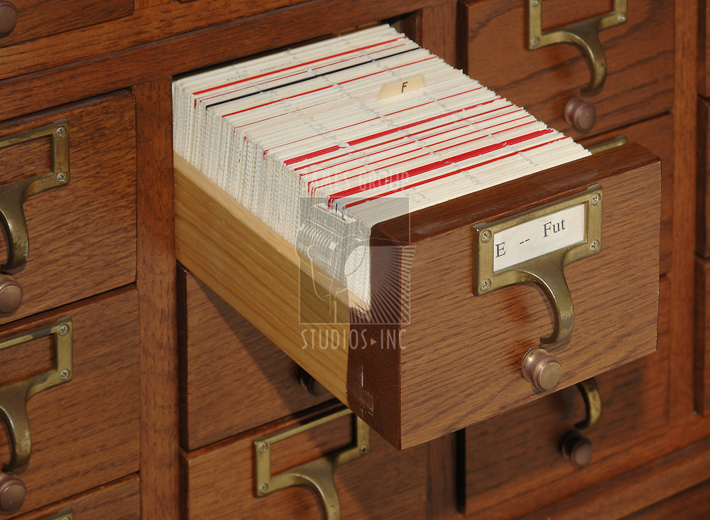 Oak card catalog file with one drawer open