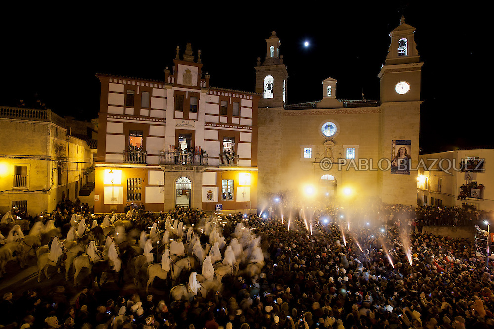 "Horsemen gather outside the church as revelers shoot blanks during the ""La Encamisa"" Festival on December 7,  2014 in Torrejoncillo, Extremadura region, Spain. ""La Encamisa"" is an ancient festival in honor of Immaculate Conception. Hundreds of horsemen wearing a white sheet gather outside the church in the main square. The procession starts when a banner with the image of Immaculate Conception is delivered to the horse rider steward and people cheer and shoot blanks. There are bonfires along the way where people gather to chat, eat traditional sweets and drink local wine. The origin of this tradition is unknown but it is believed the festival comes from a military event in which people from Torrejoncillo were involved. The war in Flanders in 1585, the Battle of Pavia or a legend of the siege suffered by city of Coria. (© Pablo Blazquez)"